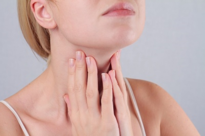 woman feeling her neck for mass links to thyroid and endocrine surgery
